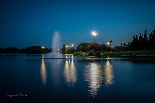 Bud Miller Park at night with the fountains on in the lake, Lloydminster, AB