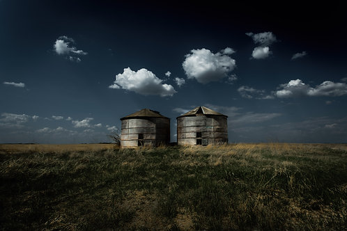 Two grain bins on the prairie against a sky with fluffy clouds