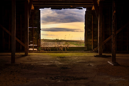Looking out at the sunrise through the doorway of an abandoned barn on the prairies.