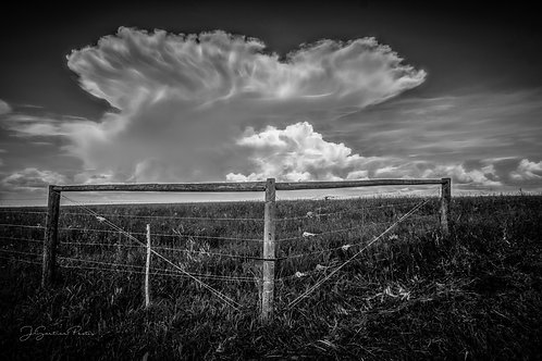 Interesting white clouds behind a corner of barbed wire fence in black and white.
