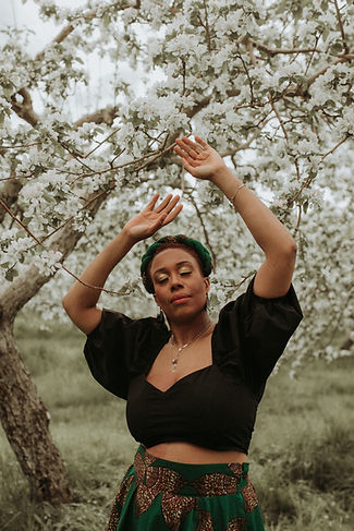Lindsay of Sucre Brun with her hands up under an appletree with white flowers