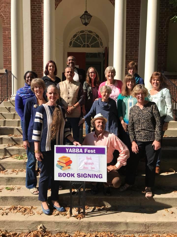 Group of authors standing with sign in front of library
