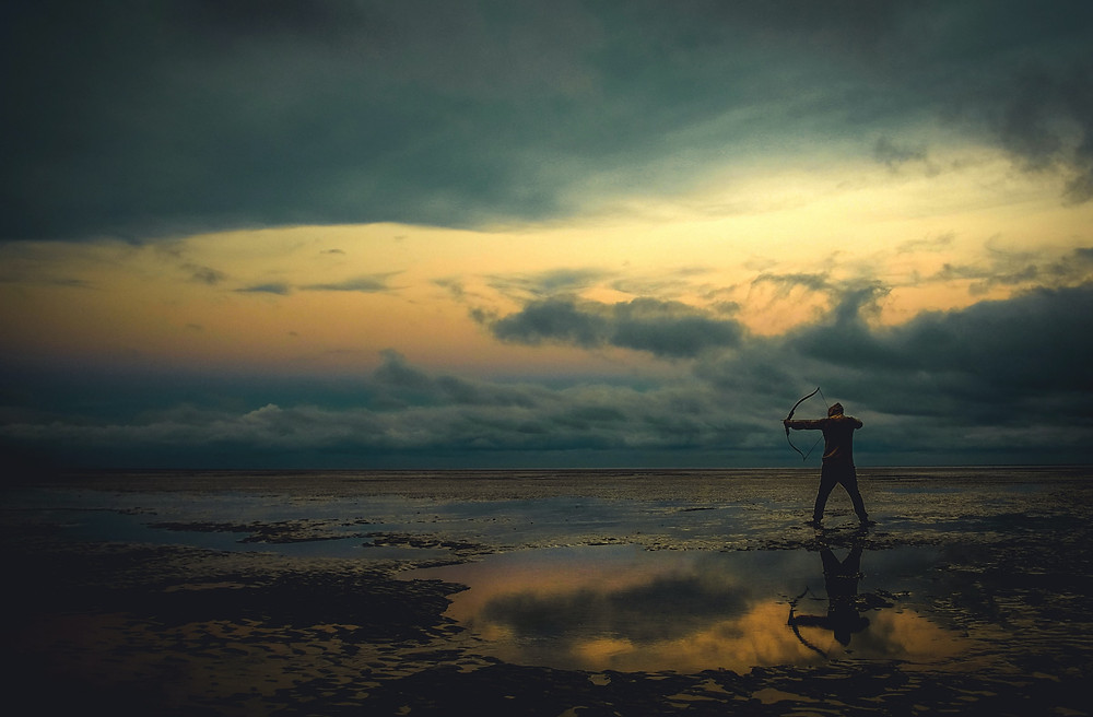 Man aims a bow while standing near reflective pond, and below heavy clouds with peaks of sunlight, credit Zoltan Tosi