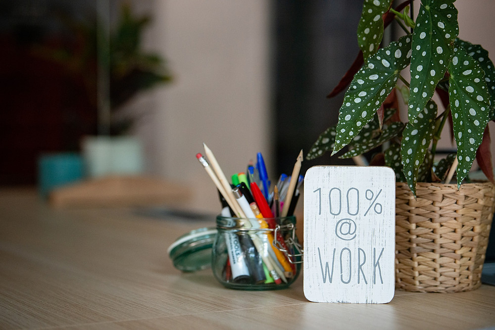 "Desk with plants, jar of writing utensils and ""at work"" sign, credit: Anke Sundermeier"