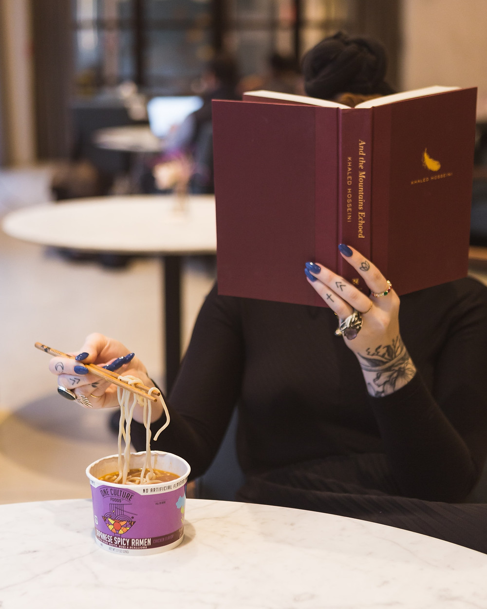 Woman with hand tattoos at table reading while eating sushi (credit: Creative Commons)