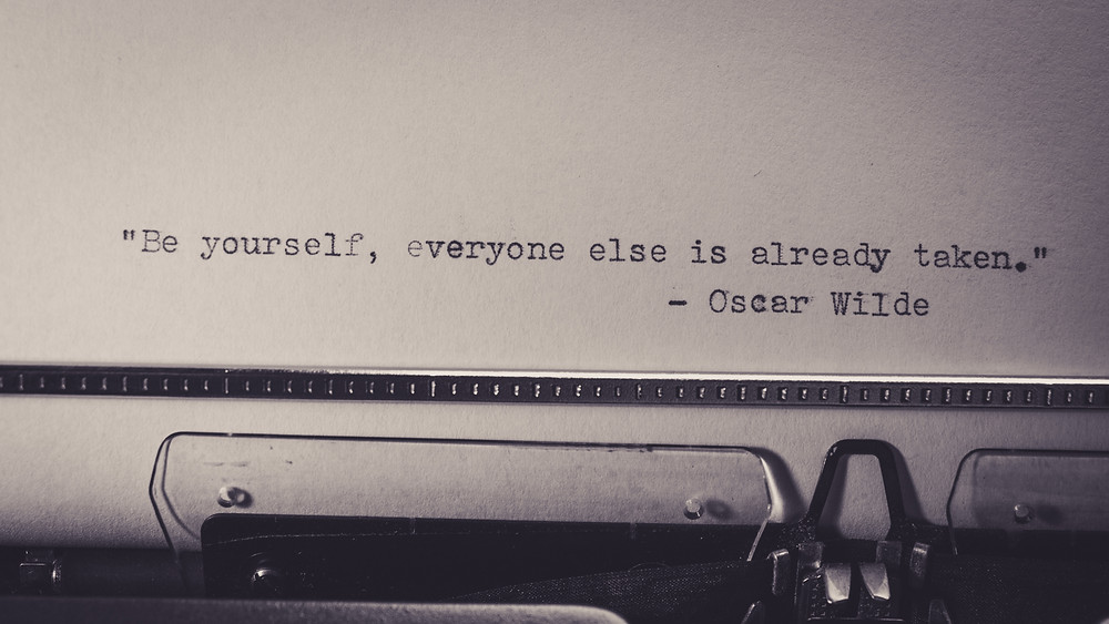 """Oscar Wilde quote,""""Be yourself, everyone else is taken"""" typed onto a piece of paper by a typewriter ."""