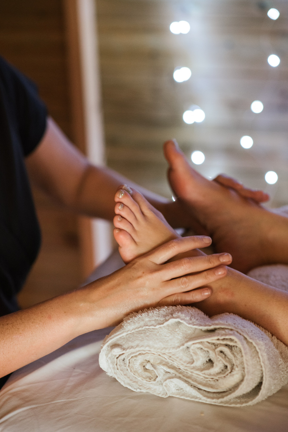 Massage therapist touches the feet of a client on a table. Credit, Anete Lusina.