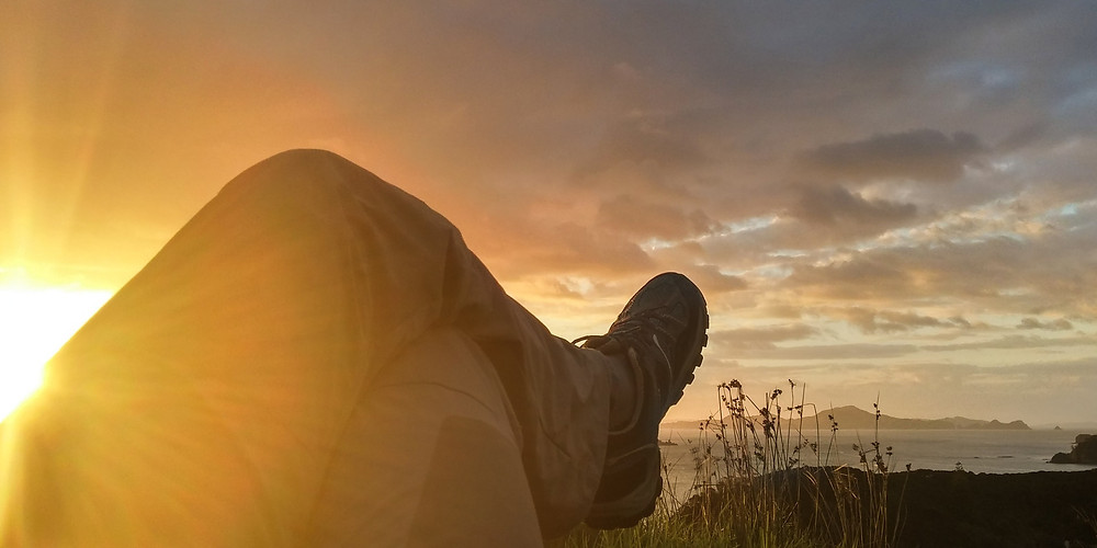 Shows the crossed legs of someone lying down enjoying a sunrise, by Lachlan Ness