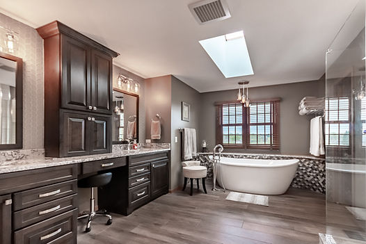 Luxury master bathroom remodel with large soaking tub and dark cabinetry