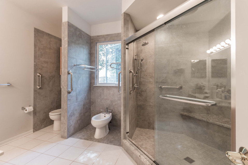 Ugly duckling bathroom with two toilets and large shower