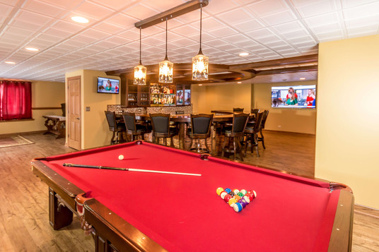 Basement remodeled into game room with bar and pool