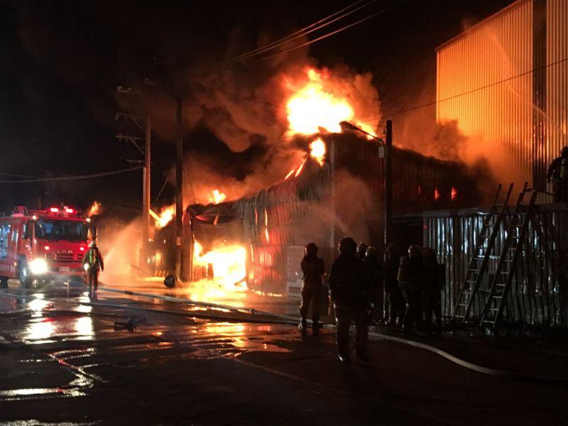 桃園市蘆竹區一家工廠14日凌晨發生大火,消防隊緊急救出5名外籍移工送醫,但現場疑似仍有6名員工受困。(中央社/桃園市消防局提供)