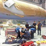 飛機艙門因氣壓彈開撞翻升高機,以致2名維修員從高處墜落受傷,救護人員緊急搶救。翻攝畫面