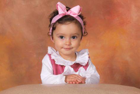 menina de laço cor de rosa em cenário de estúdio fotográfico