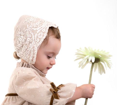 Criança agarrando flor em sessão fotográfica