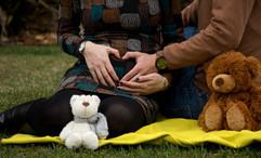 Coração com mãos de pais na barriga de gestante
