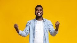 joyful-black-guy-rejoicing-success-clenc