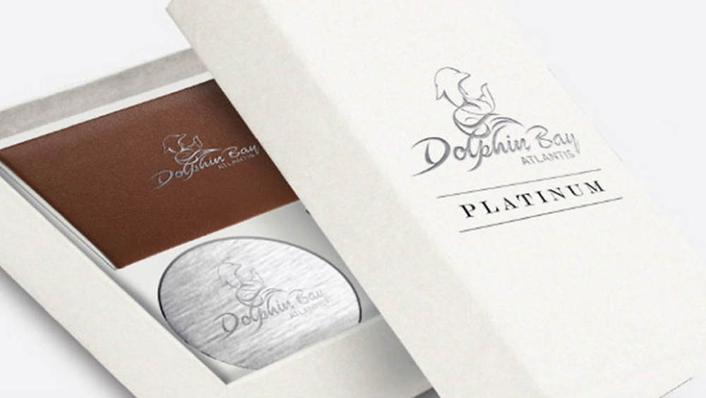 A brown leather-bound book and engraved metal tin, packaged in a white cardboard gift box with the Dolphin Bay logo in silver on top.