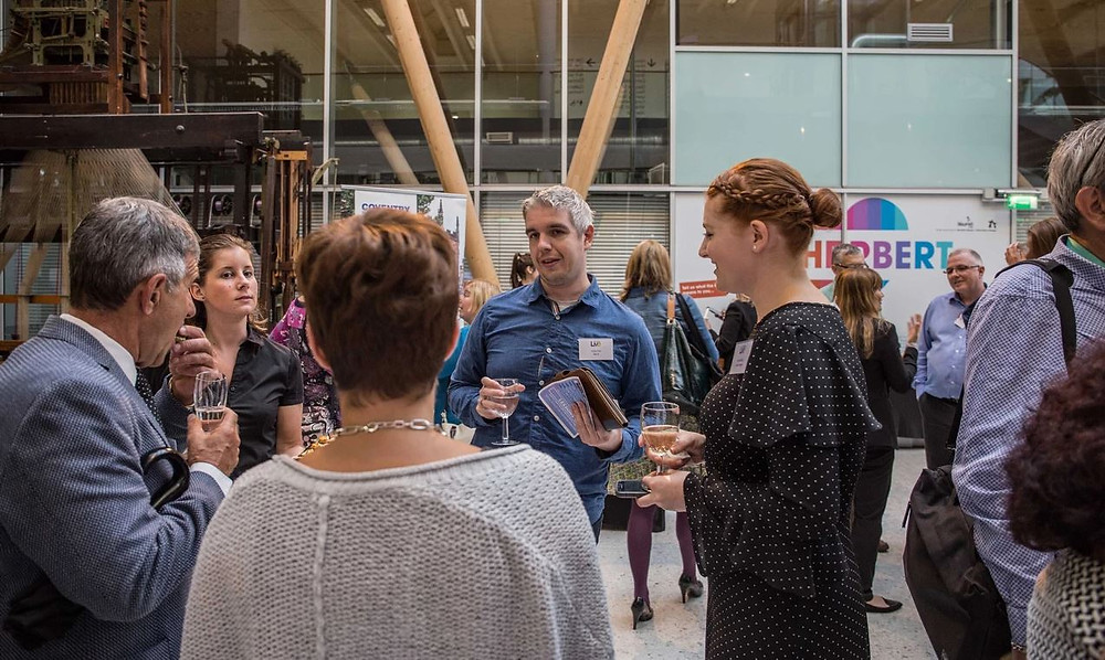 A group of people stood talking whilst holding drinks at a networking event.