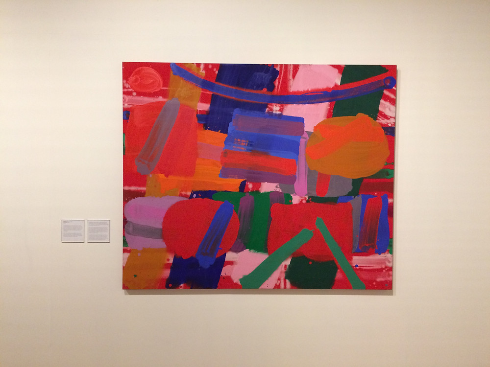A large brightly coloured acrylic painting by Albert Irvin, hung on a white with with a display card seen on the left hand side.