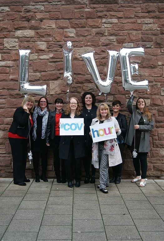 An image of eight ladies stood against a brick wall holding a #CovHour sign and four silver balloons spelling the word Live.