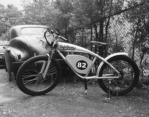 CafeRacer E-bike with vintage car in background sepia toned