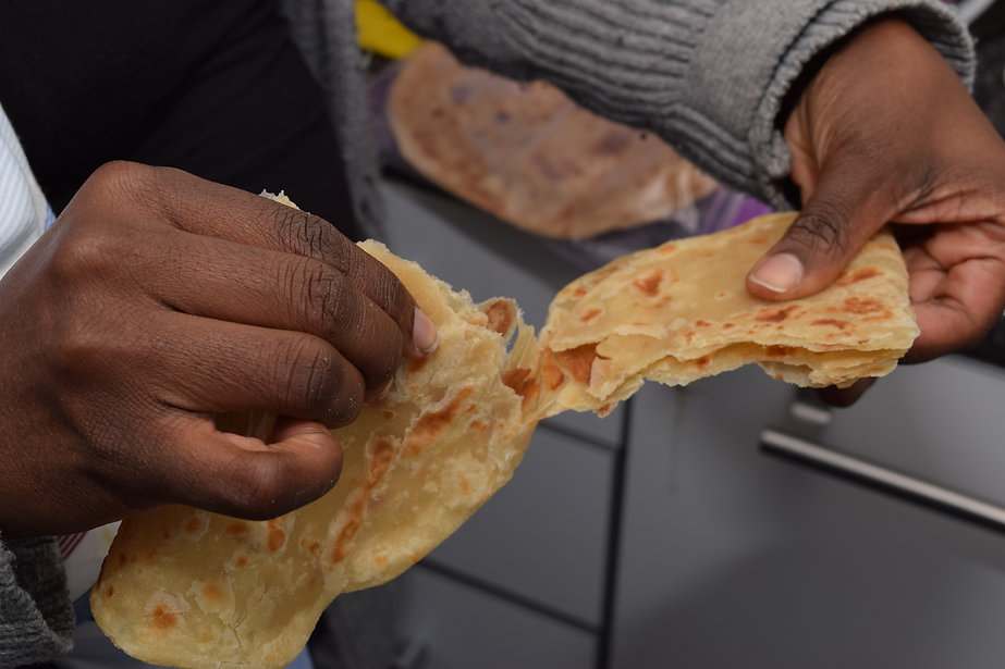 African female hands ripping a slice of