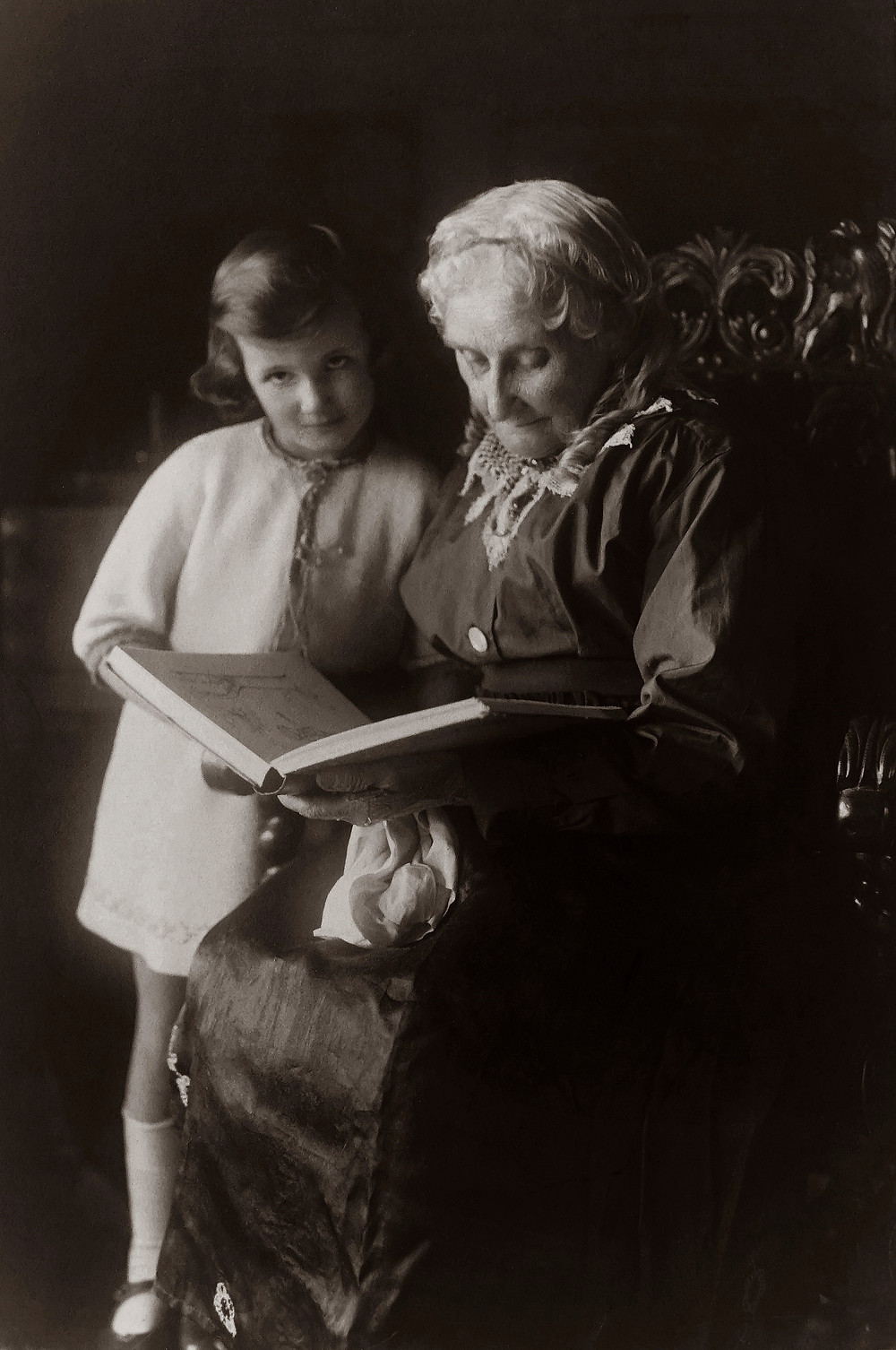 historical photo of a grandmother in the 1800s reading to a young girl