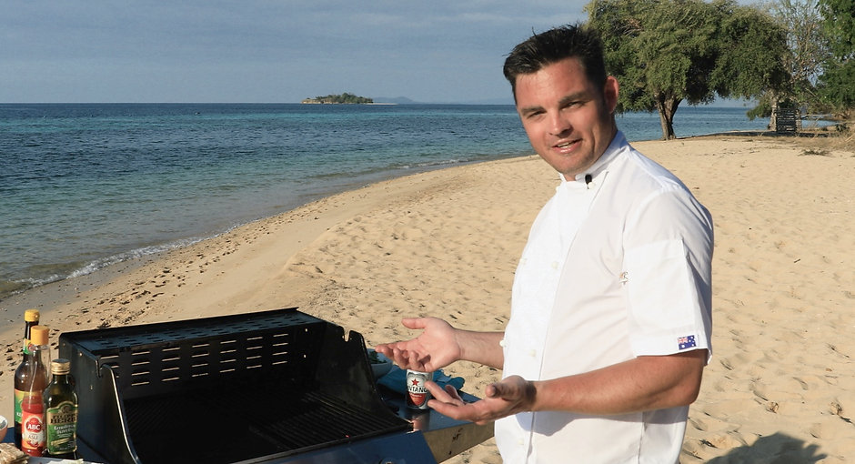 The Flying Chef cooking BBQ on beach of exotic tropical island