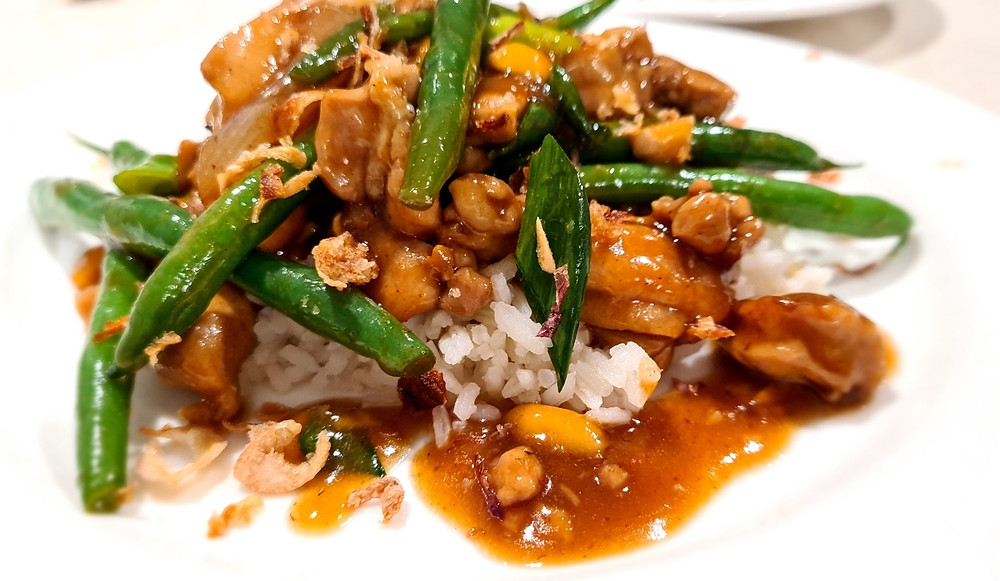 Mouth watering traditional Chinese kung pao chicken with chilies, green beans and roasted peanuts on a bed of steamed rice