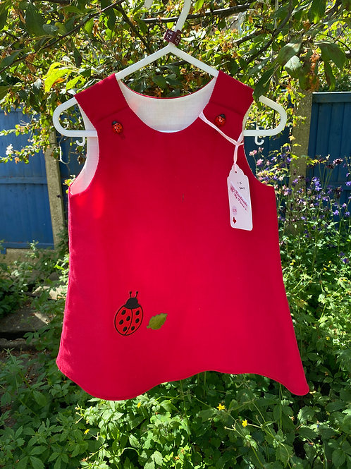 Handmade red baby needlecord pinafore dress. Age: 6-12 months.