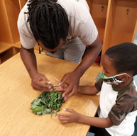Gregory Smith the garden whisperer helping a kid.