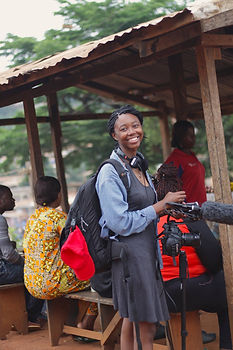Elodie Edjang smiles as she hold her camera on a monopod