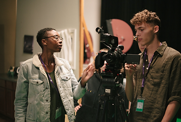 Elodie Edjang gives a hands on camera operation tutorial to young filmmakers