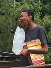 Close up of Elodie Edjang eating dry cereal in a dumpster