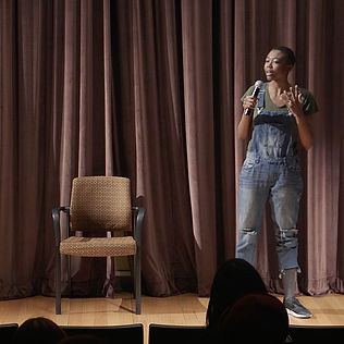 Elodie Edjang, A black woman performing stand up comedy in overalls