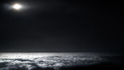 The sun peeking through a hole in the clouds