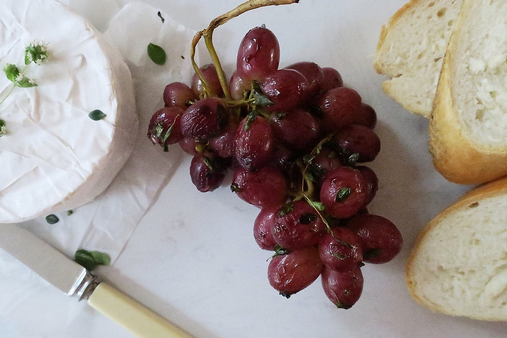 Roasted grapes on a serving platter with cheese and bread