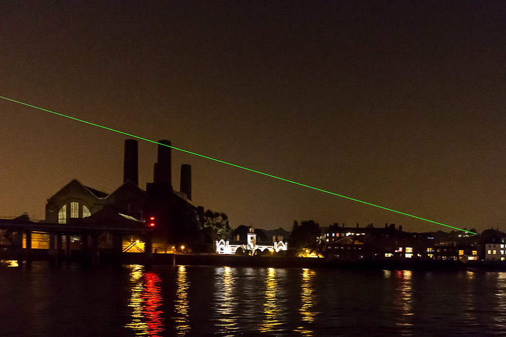 Laser at night passing over Greenwich Power station and the river Thames