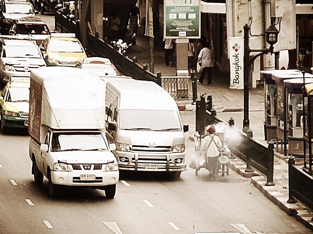 Food vendor walking down main road in central Bangkok
