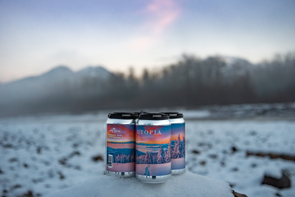A beautiful mountain sunset, featuring a four pack of sour beer with a sunset label in the snow