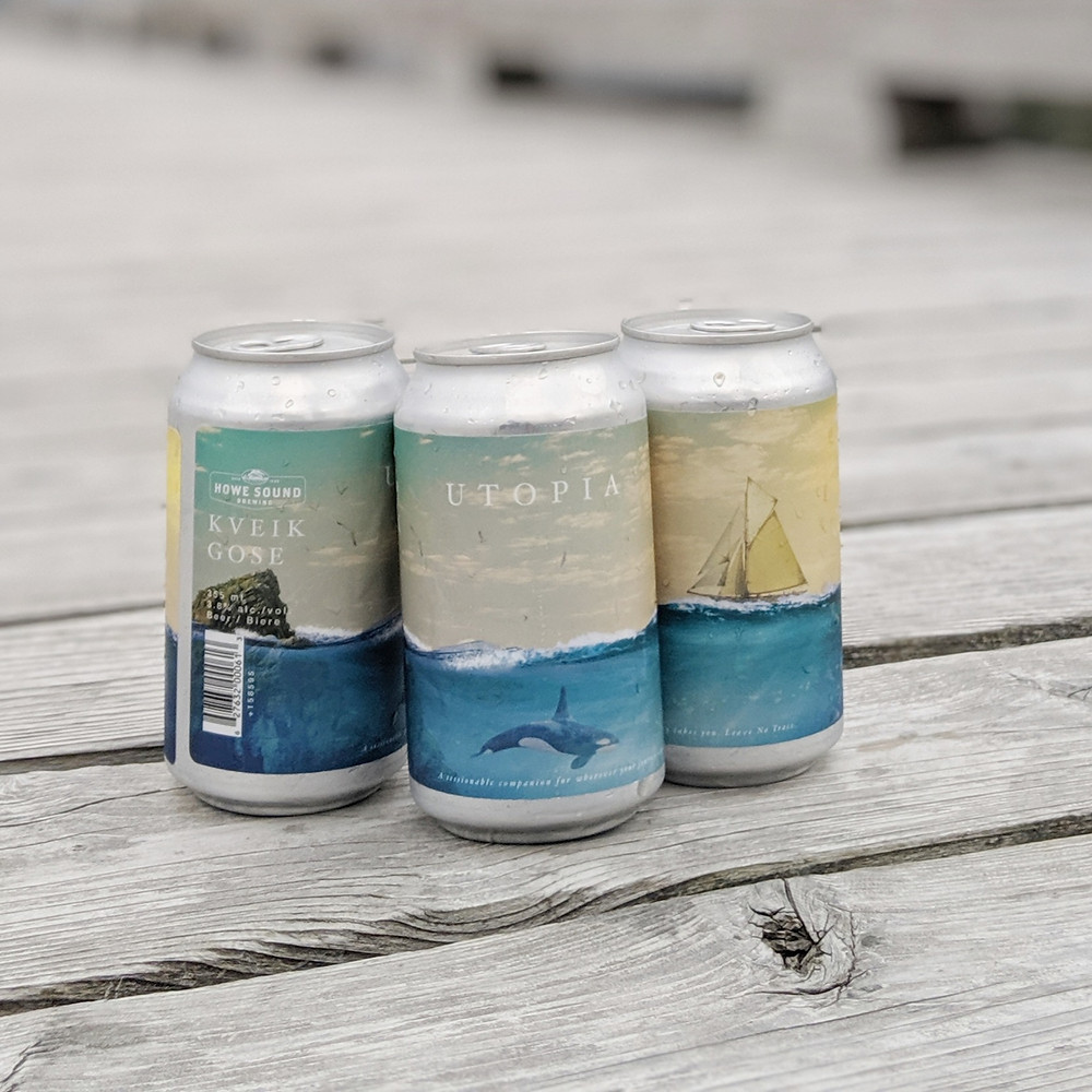Beer cans with the ocean, a boat and an orca sitting on the docks