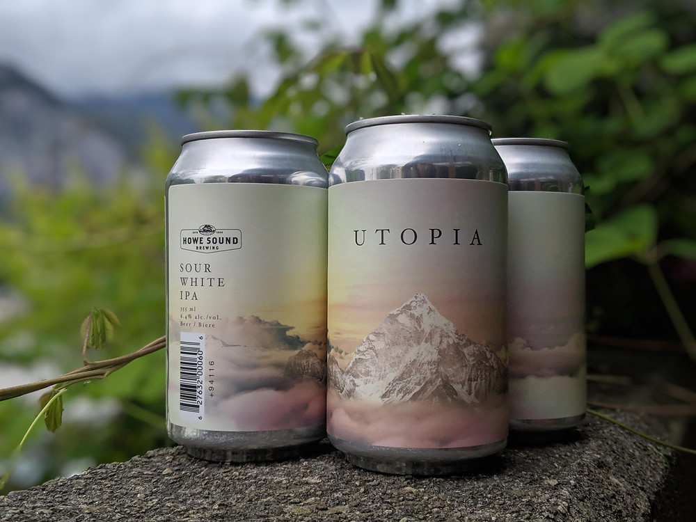 Beer can with mountain range and clouds sitting in the trees