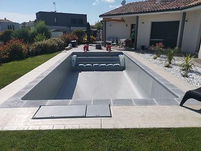 Professionnels de la piscine et constructions de bassins enterrés. Bord fait avec des margelles grises et claires.