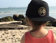 Enfant face à la mer avec la casquette Chinquante