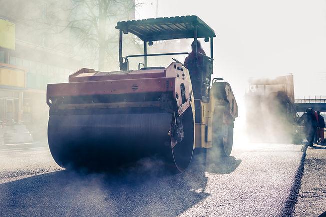 Workers making asphalt with shovels at r