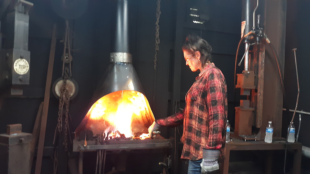 LIndy is heating her metal in the coal forge at LLForge Airbnb Learn to Forge esperience