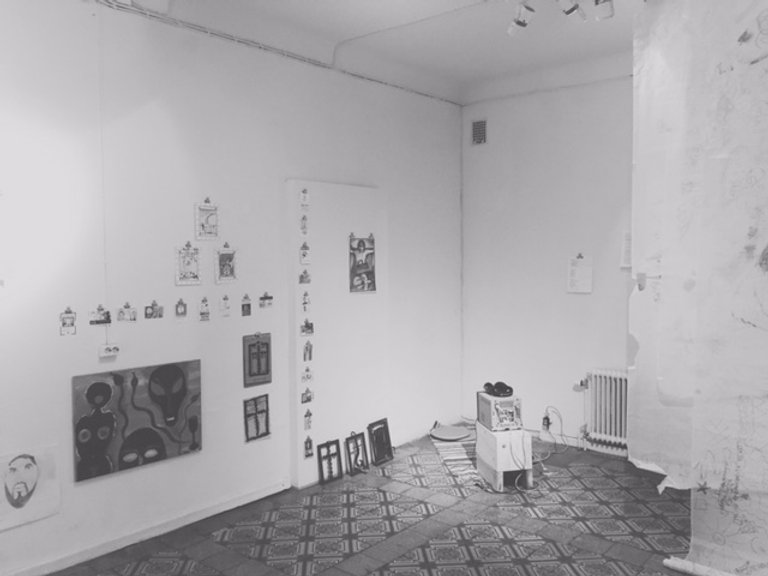 Corner of the MAA-tila project/gallery space with white walls and tiled floor. Paintings and drawings of different sizes are hanging on the walls, and a small cube TV is on the floor and headphones on top of it.