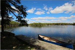 Portage canoe on lake in forest, community activities