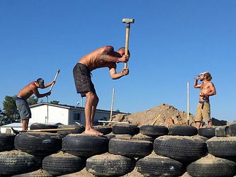 Three people ponding tires on an Earthship build in Orangeville Ontario Canada
